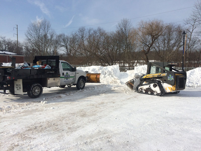 Images of New Jersey Commerical Snow Plowing company working during a snow storm plowing snow